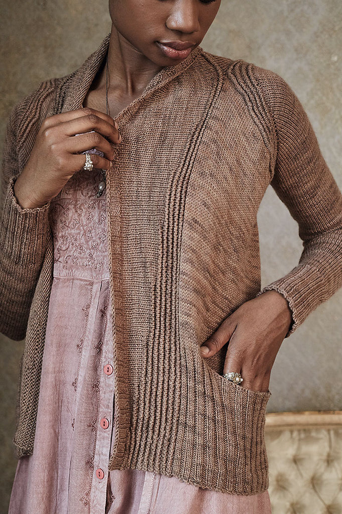 Image of a black woman wearing an open cardigan. Her hand is in the pocket which is placed in deep ribbing.
