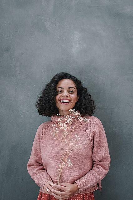 Image of a light brown skinned woman wearing a light pink jumper with a branching detail along the raglan line