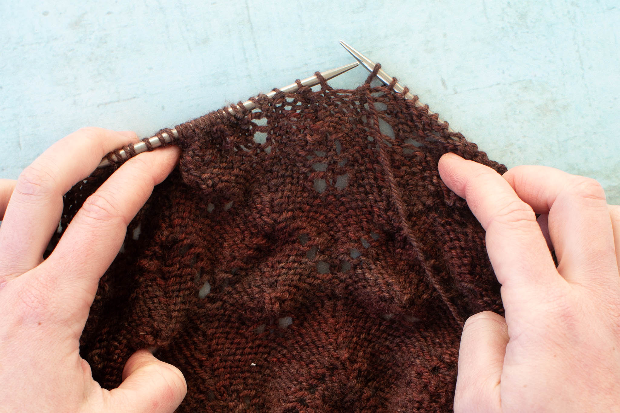 a brown shawl is being spread out on the needles with the wrong side facing