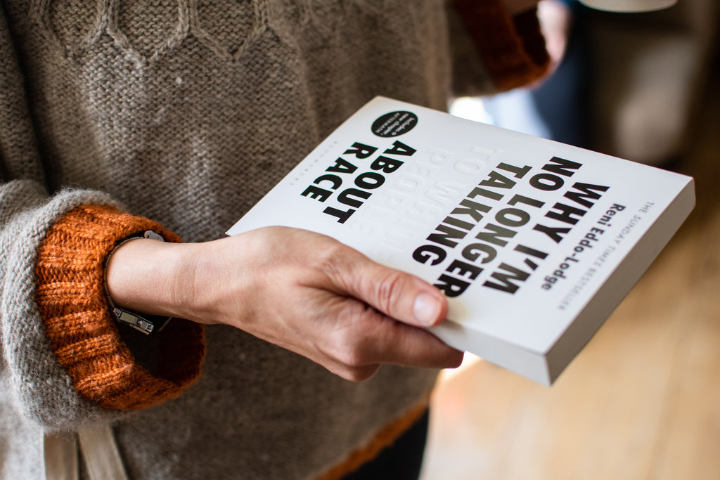 Hands holding a copy of a white covered book titled 'Why I'm No Longer Talked to White People About Race' The Text is in Black except for the Words 'To White People' which are in embossed white letters