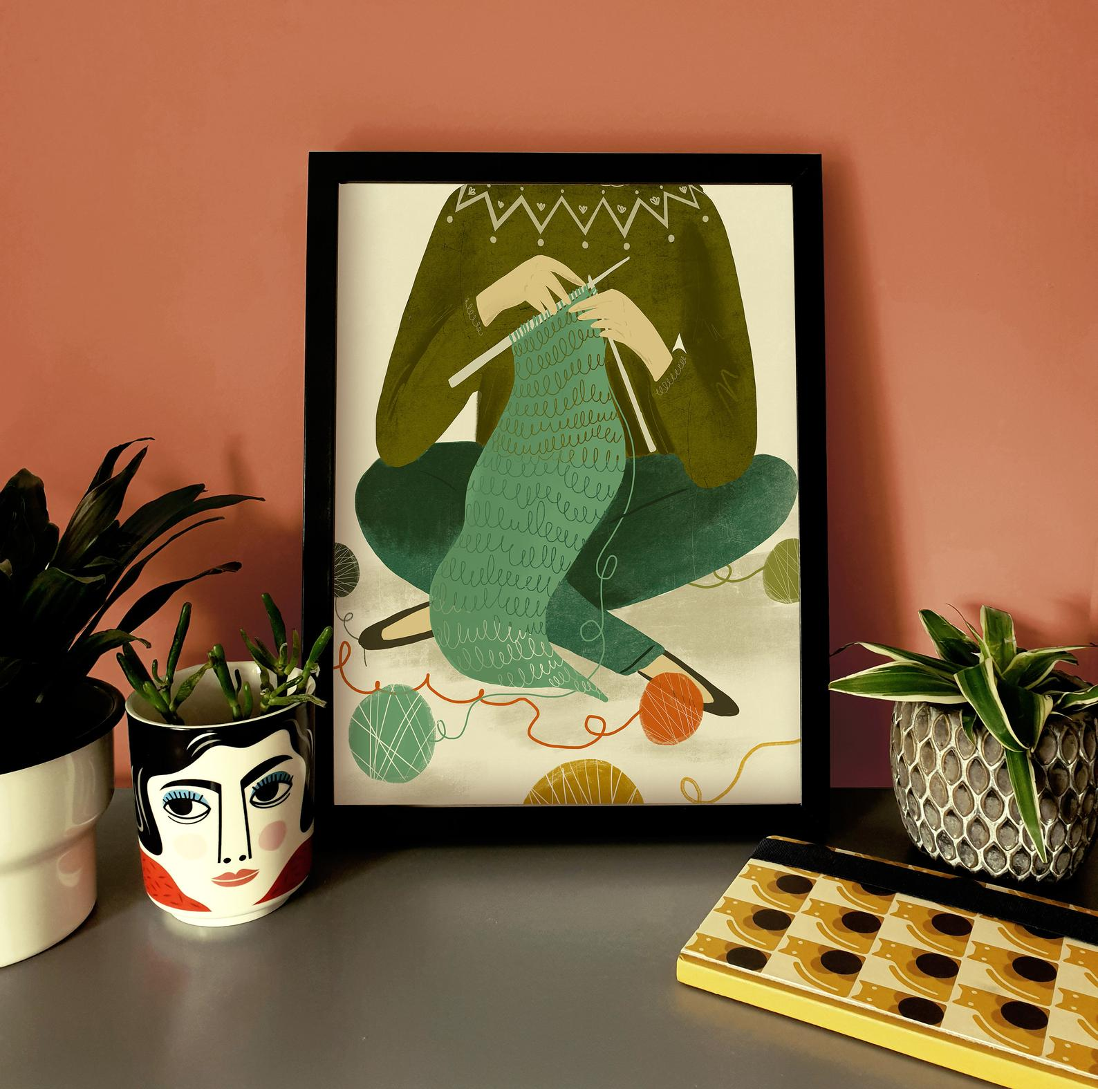 A print of a knitter from the shoulders down sitting cross legged and knitting a green scarf on straight needles. Next to the framed print are houseplant in pots.