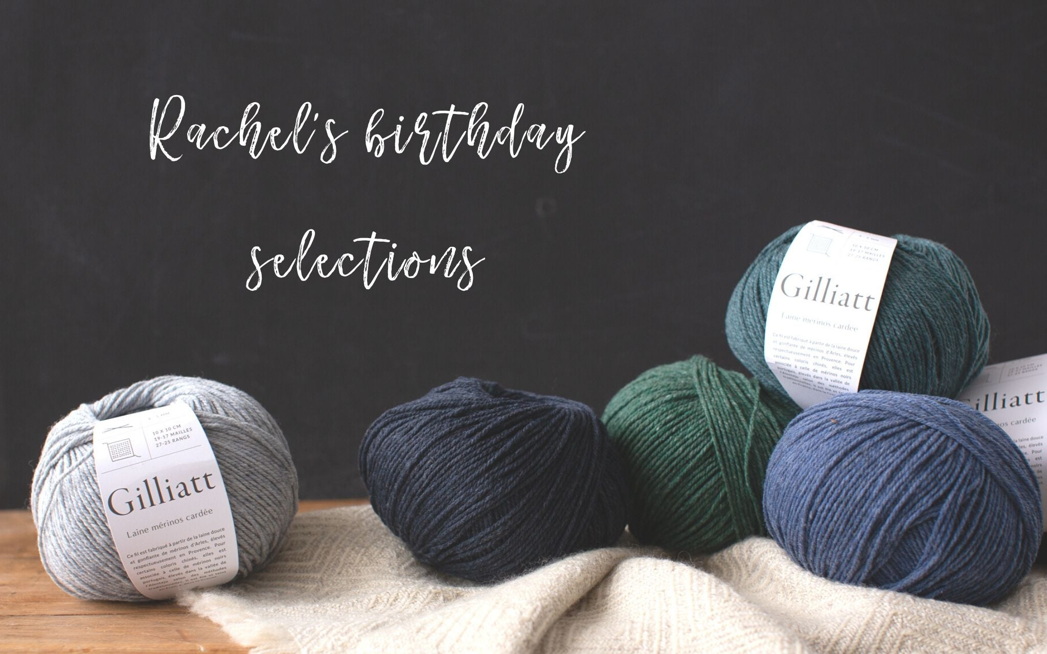 White text on black chalkboard back ground 'Rachel's birthday selections' overflowing basket of balls of yarn on a wooden table.