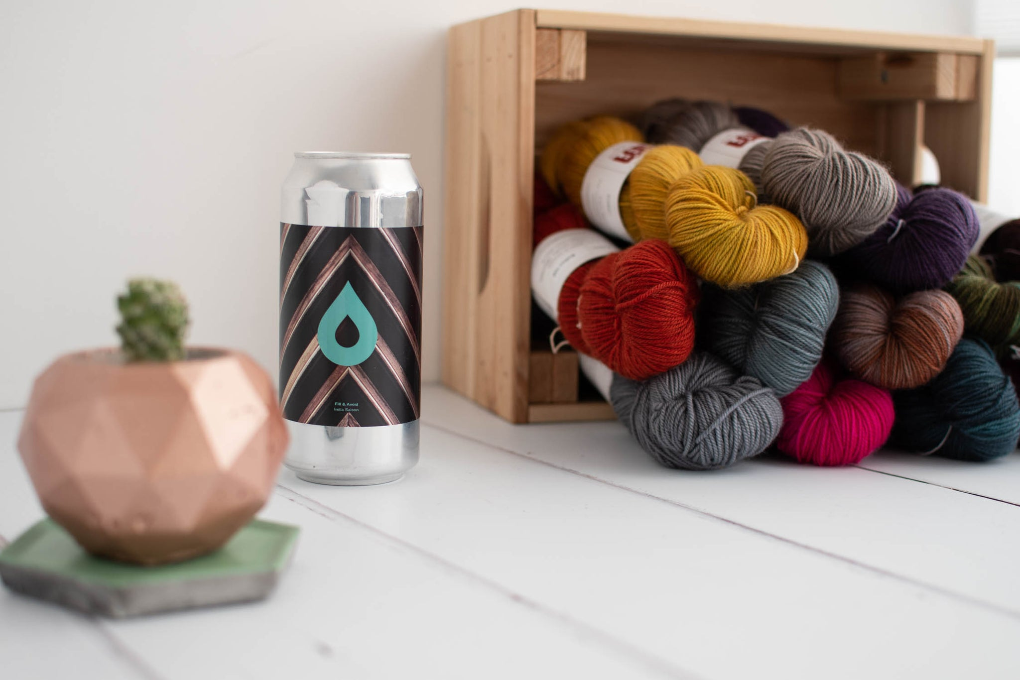 A beer can, a cacti in a geometric pot and a collection of hand dyed skeins sit on a white table in front of a white wall.
