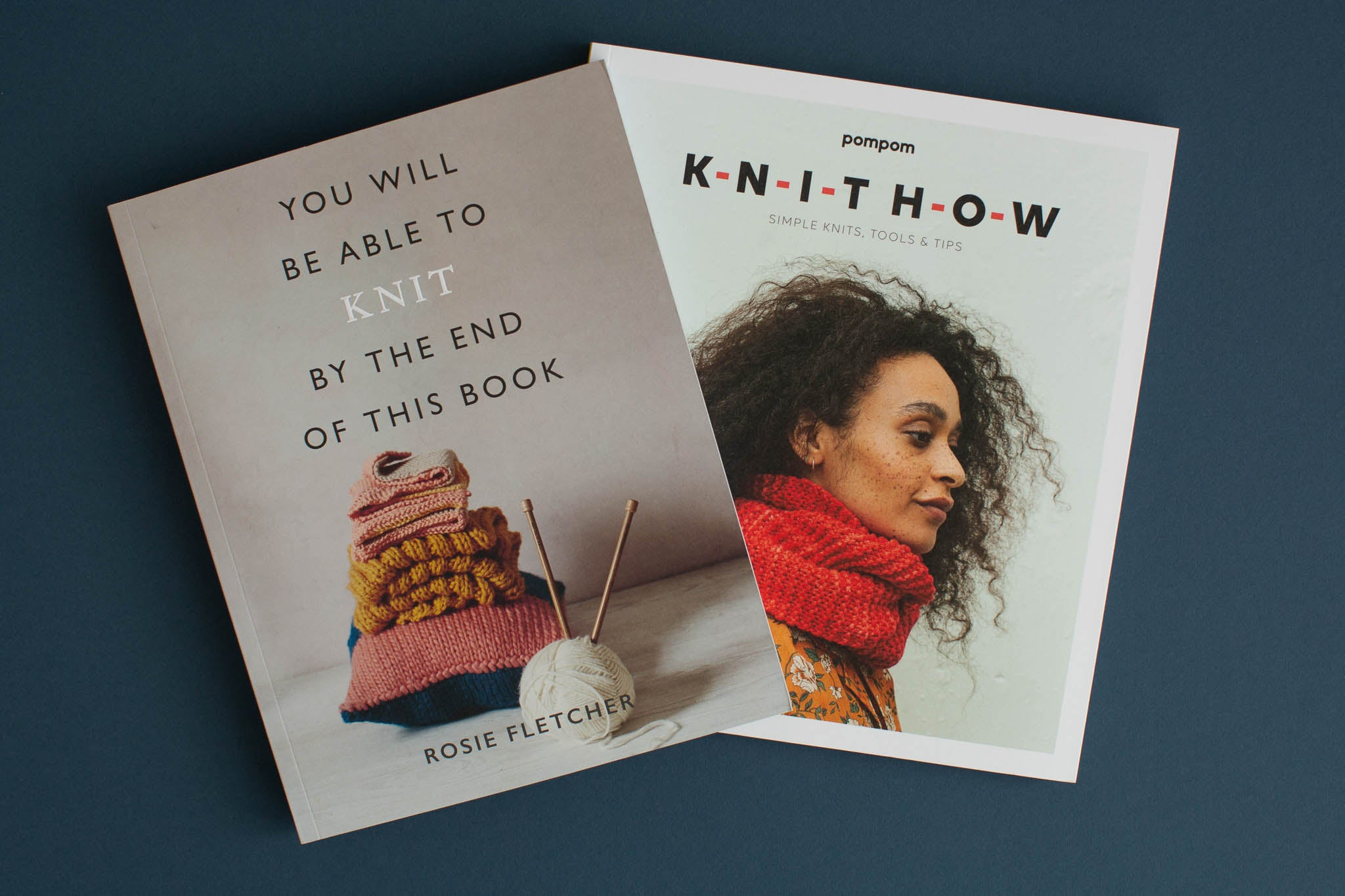 Two books laying flat, slightly overlapping. One shows a pile of knitting and is called 'You Will Be Able To Knit By The End Of This Book' and the other shows a young black woman wearing a red cowl called 'Knit How.'