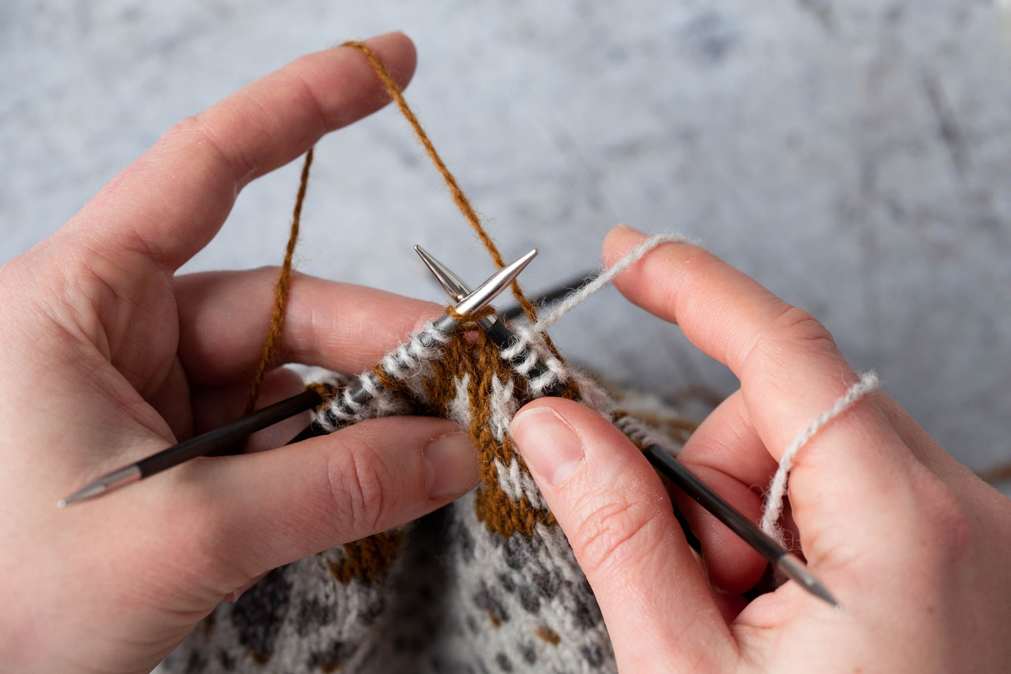 Preparing to catch a longer float across the back of the work. The yarn to be caught is in the left hand.