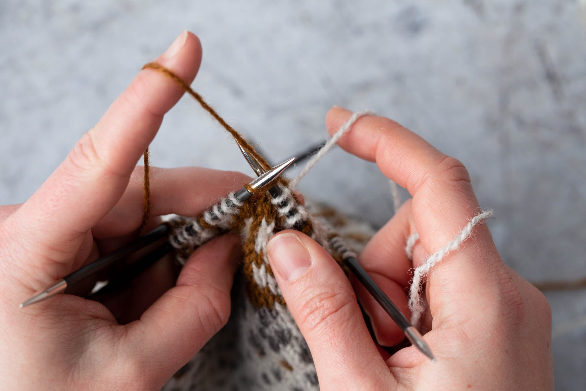 Bring the yarn to be caught over the right needle from back to front.