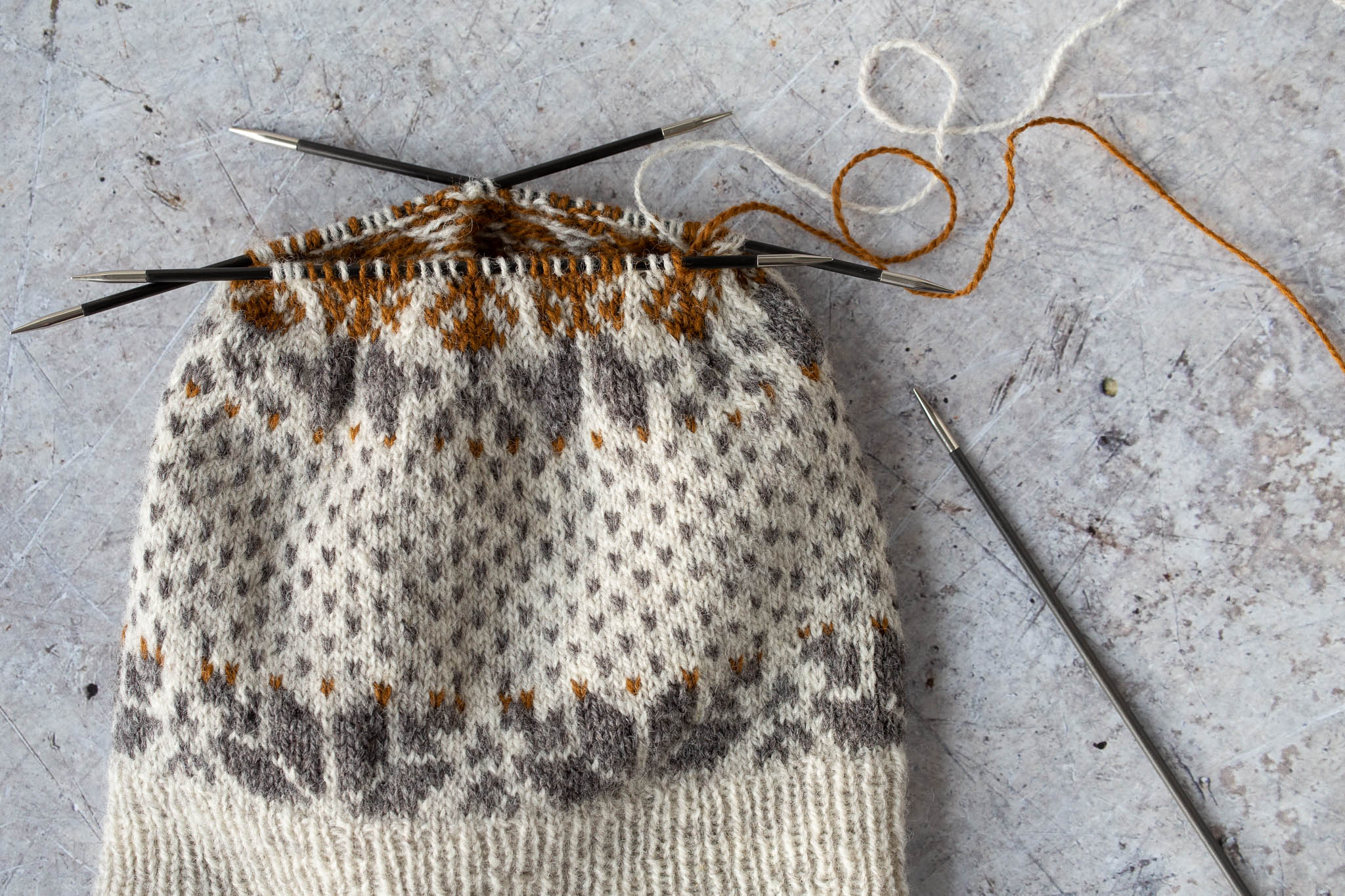 Colourwork hat in progress in beige, grey, and caramel, laid flat on a concrete floor. Stitches are divided over 3 double pointed needles.