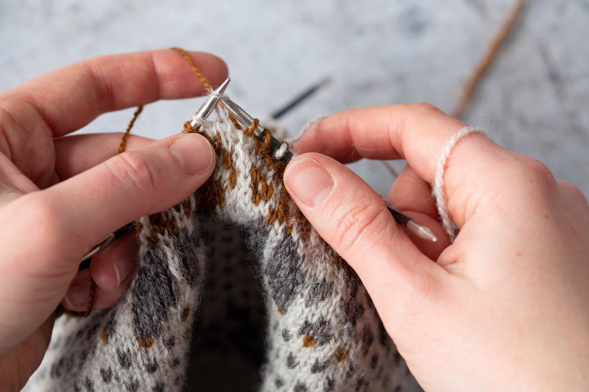 Stranded knitting with one colour in each hand. The next two stitches will be worked as ssk.