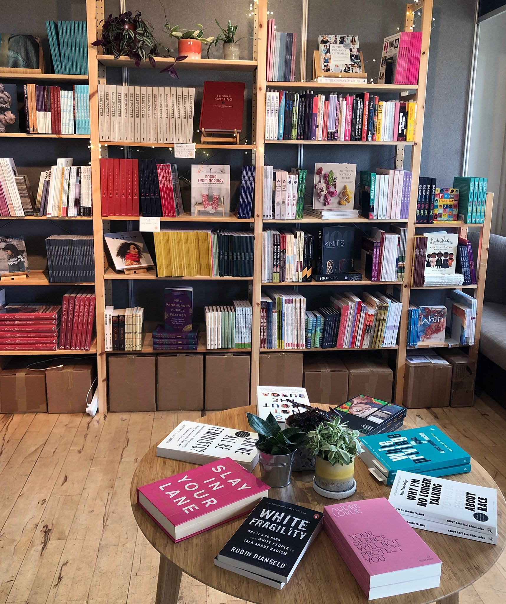 Books arranged on a round table in the foreground with shelves of books and plants in the background