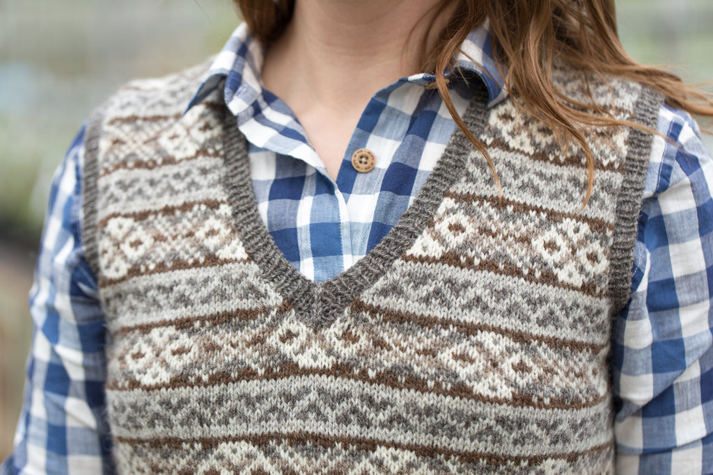 Image of a white skinned woman wearing a fair isle vest over a checked shirt, it is cropped to show the v neck and shoulders