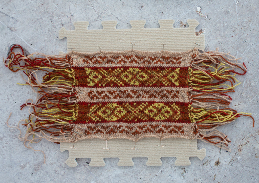 image of a red brown fair isle swatch pinned to a blocking board