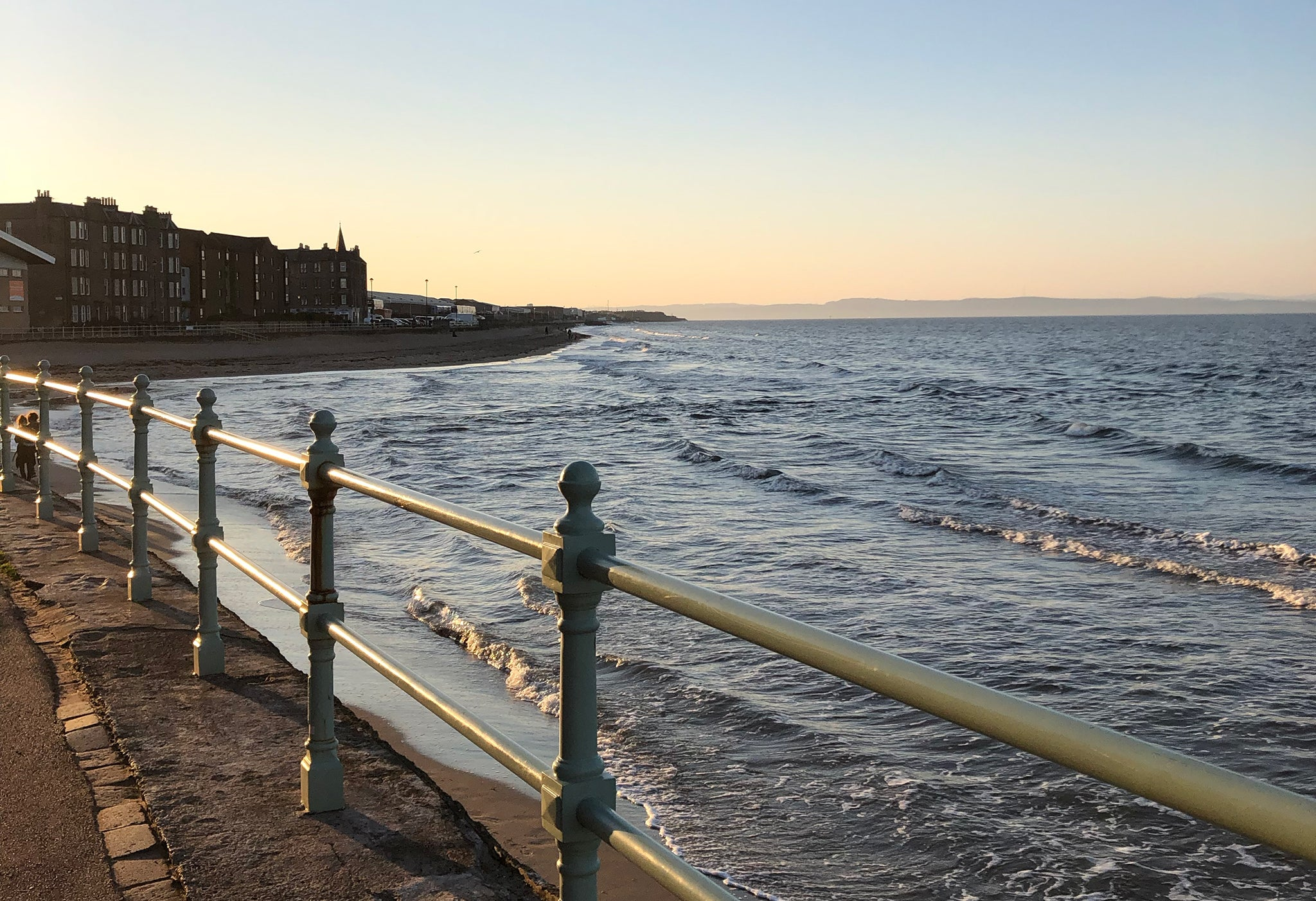 Image of the sea over an iron fence, the light is golden as the sun is about to set.