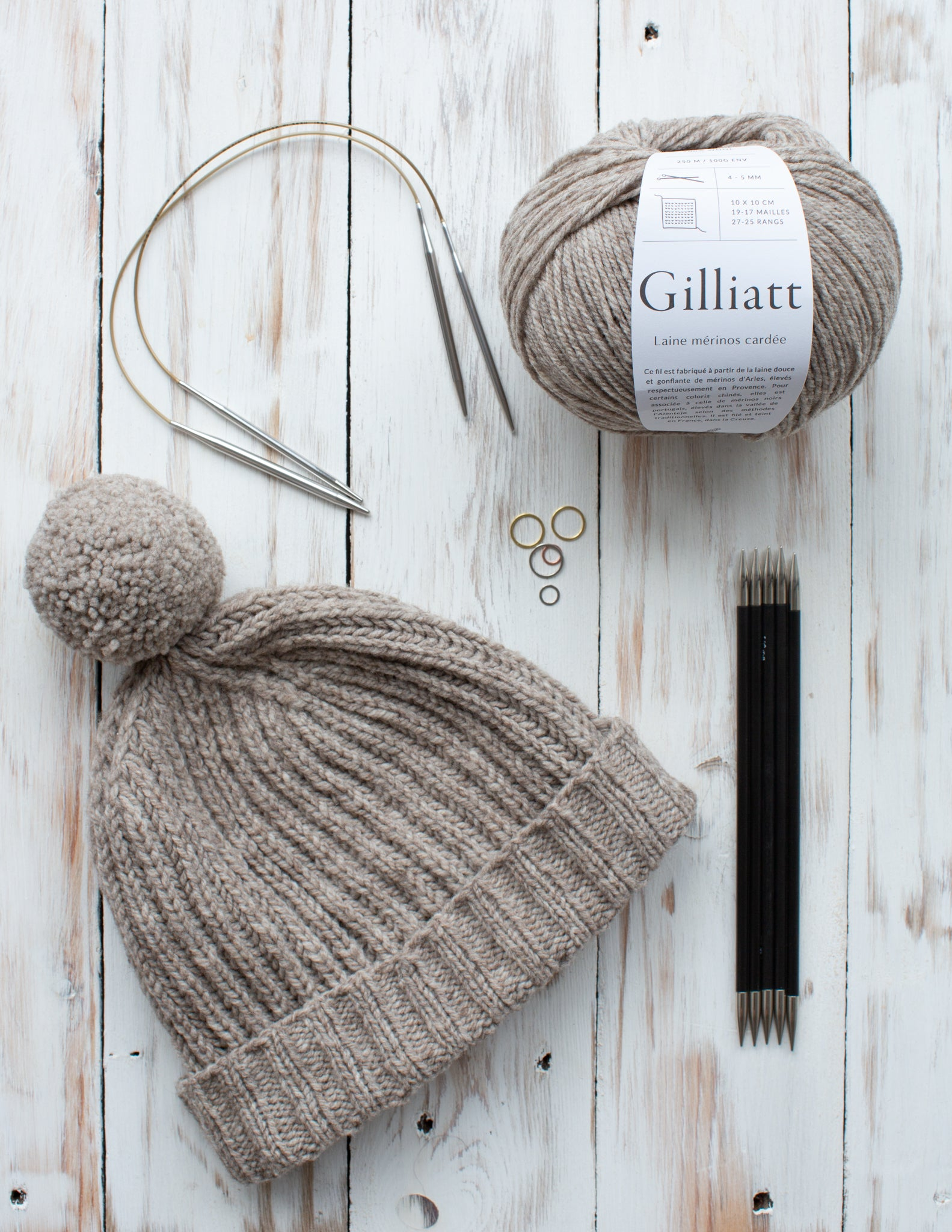Flat lay of an oatmeal coloured hat with pompom, with needles and yarn shown alongside.