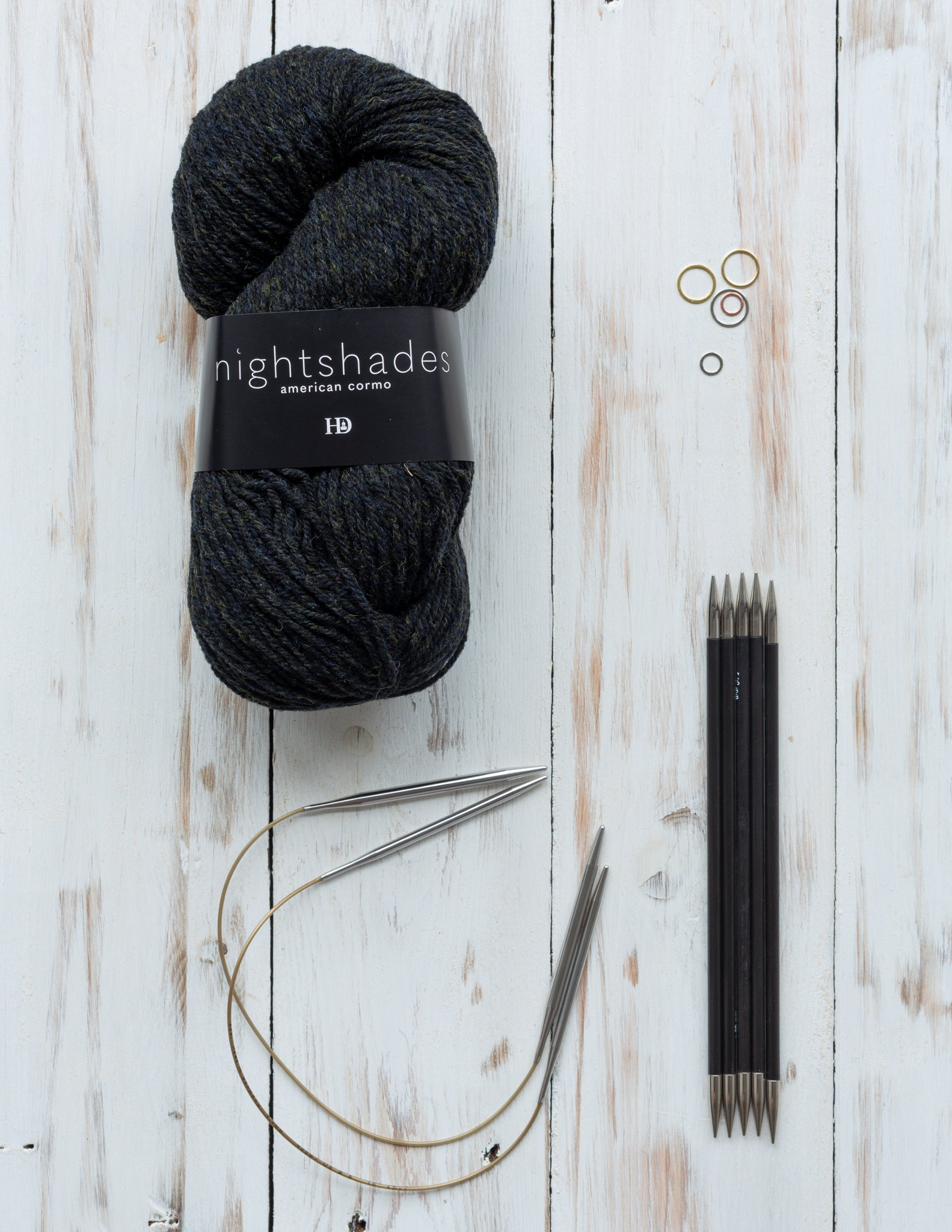 A skein of Harrisville Nightshades, with circular and double pointed needles on wooden surface