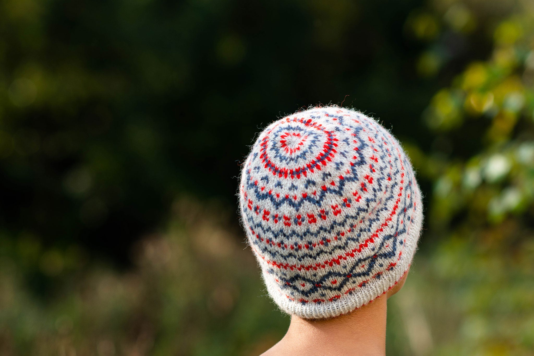 A model stands outdoors wearing a colorwork hat. Only the back of the teal, red and cream hat is visible and the background is blurred green.