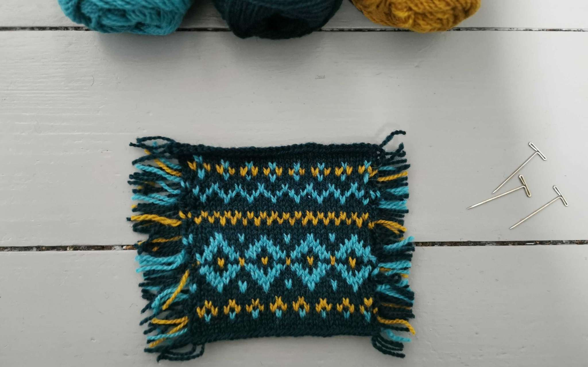 a square knitted swatch in navy, gold and teal colourwork. Three balls of yarn peak out at the top of the image and lay on a grey wooden surface