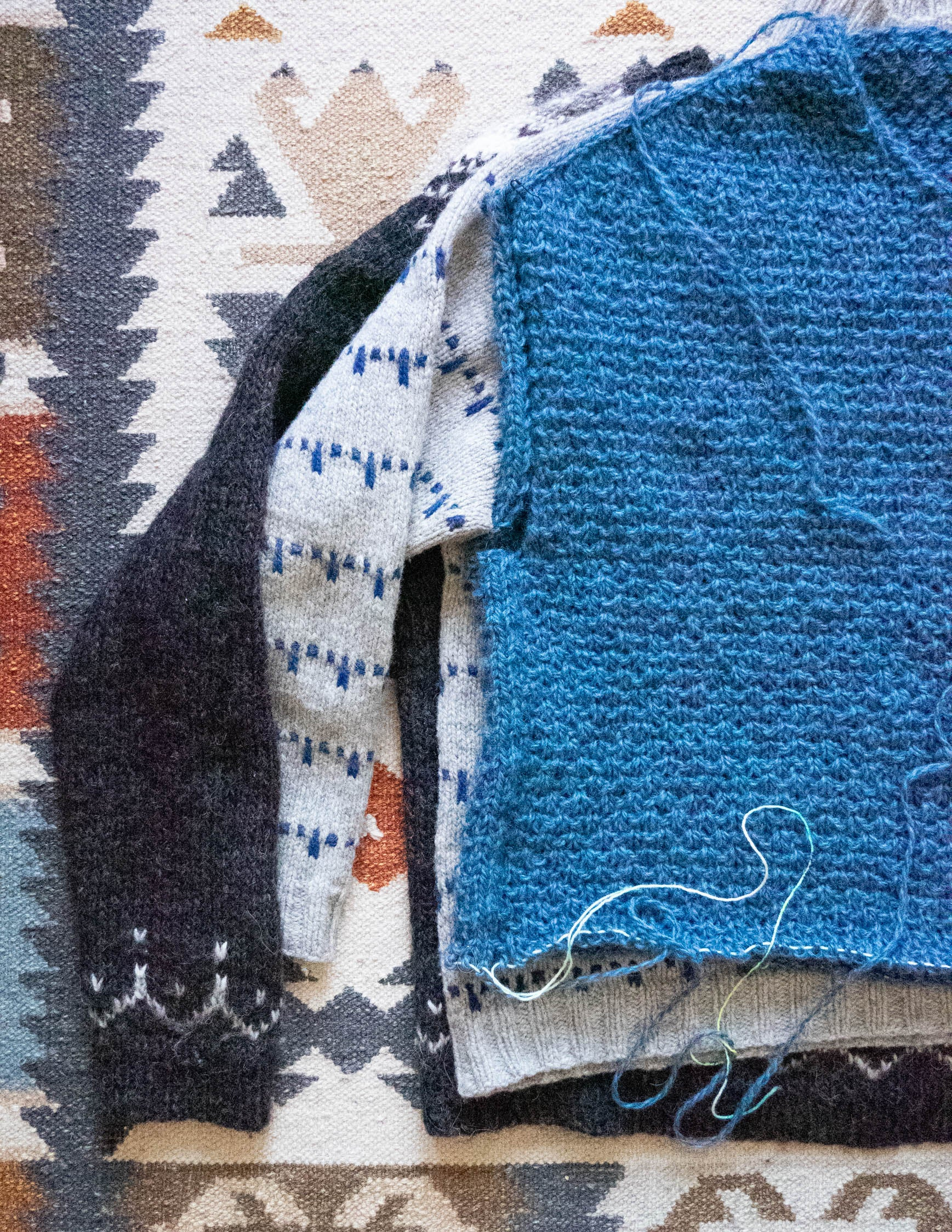 Flat lay image of 3 sweaters laid out on top of each other, to compare the length from underarm to bottom edge. The top sweater is blue and is unfinished at the bottom edge.