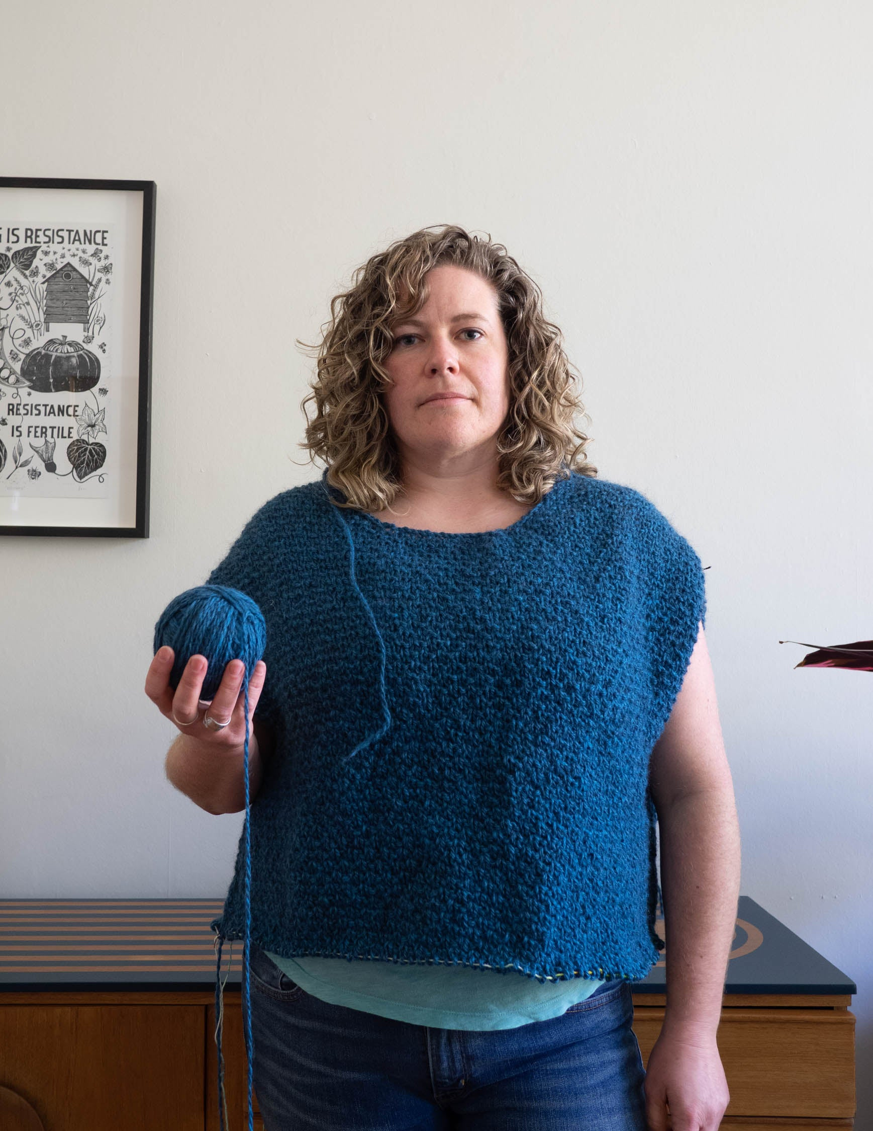 A white woman with curly hair stands looking at the camera. She has a blue textured sweater on that is in progress, the bottom edge is unfinished and it is sleeveless.