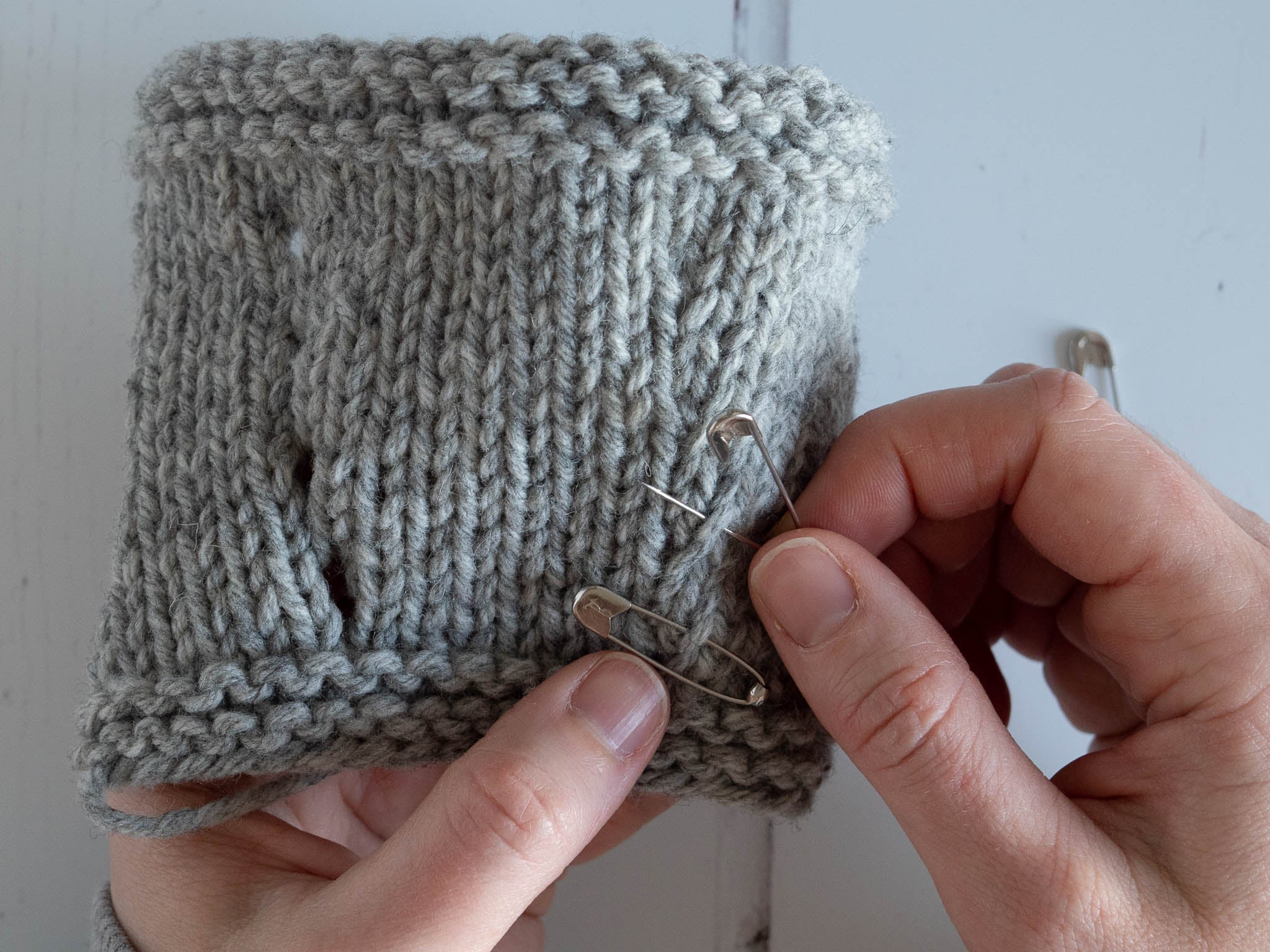 locking stitch markers shown marking increase on a grey knitted swatch