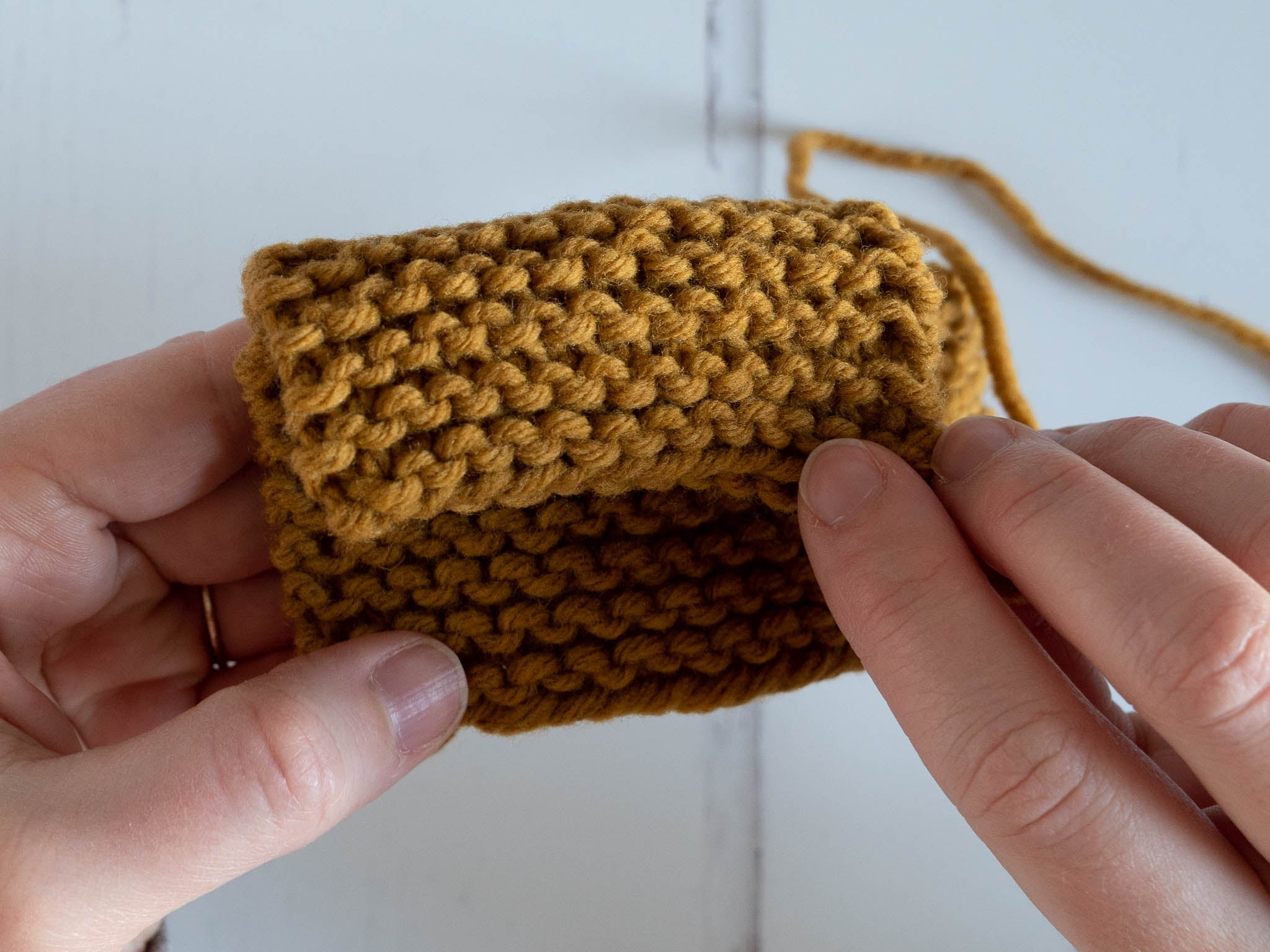 a garter stitch swatch folded over to show both sides