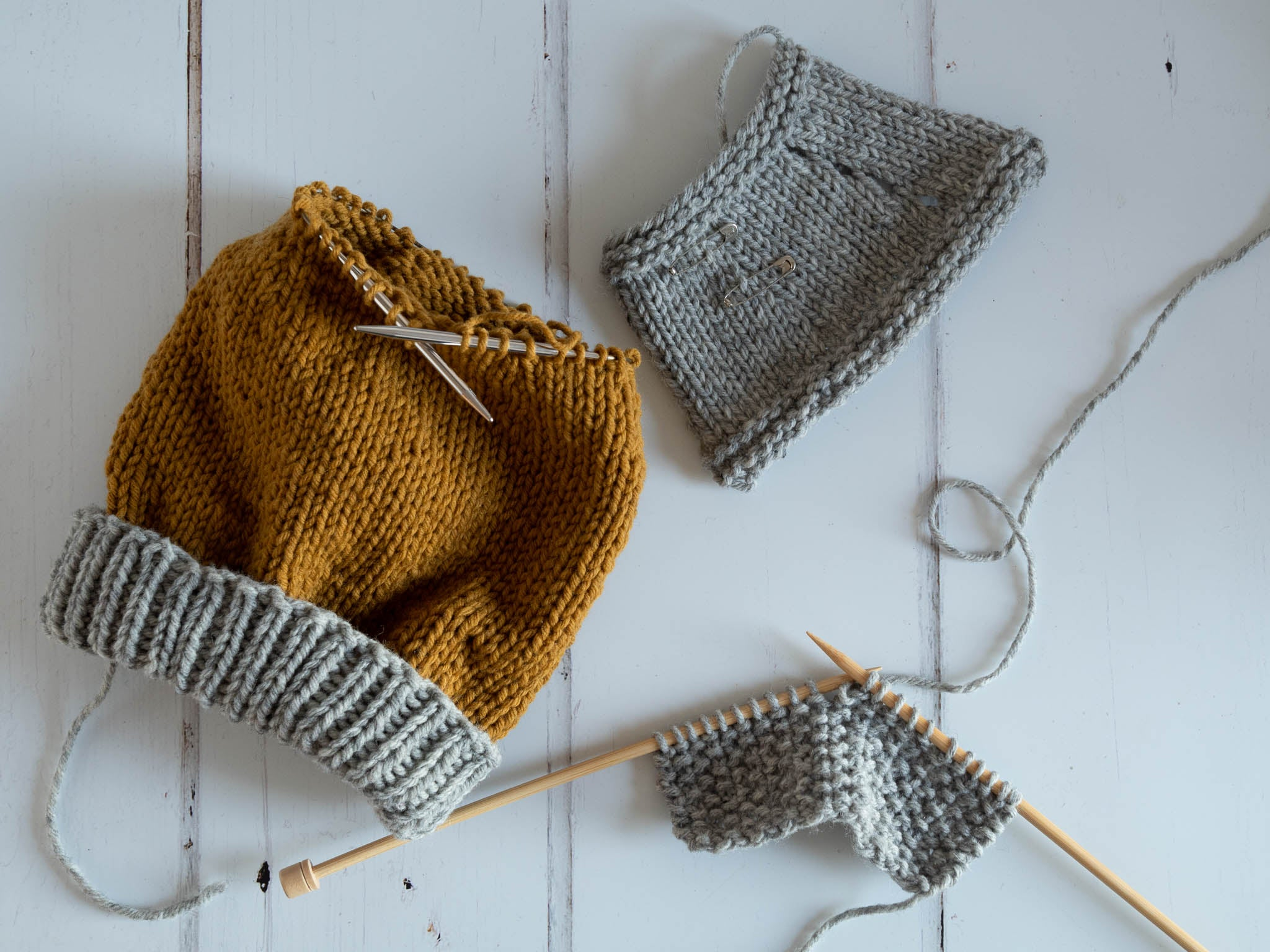 three pieces of knitting laying on a flat surface, two of which are grey swatches and one is a project in the round with a grey ribbed brim.