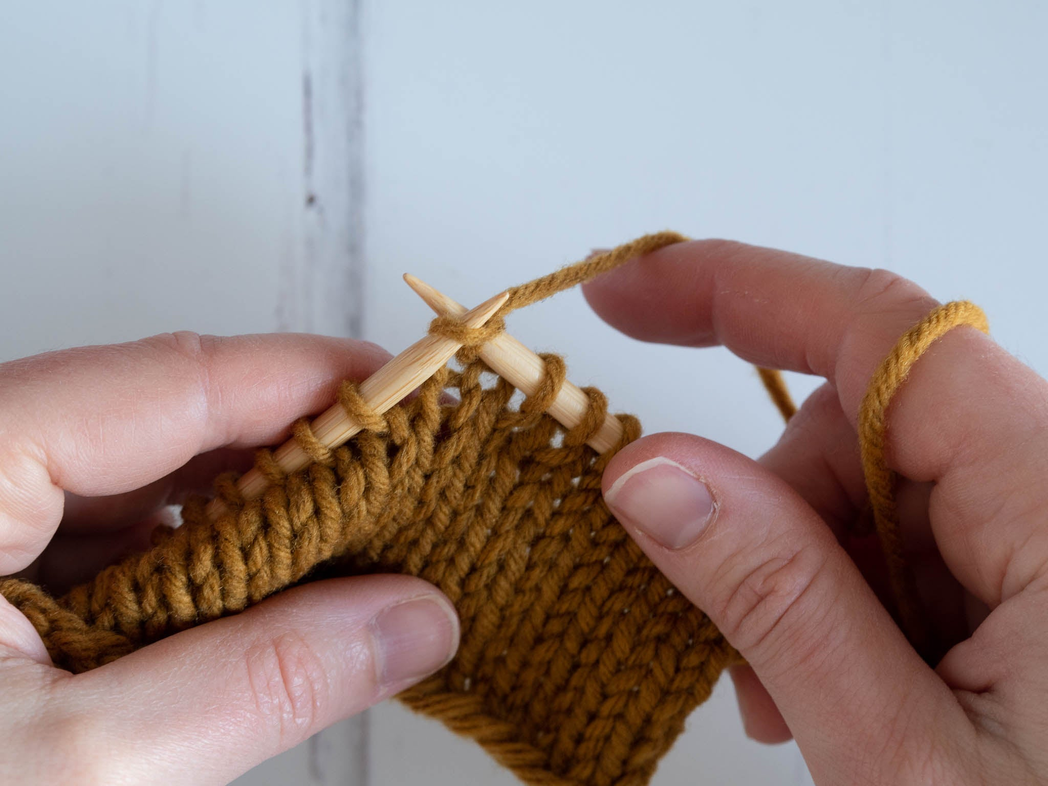 working a knit stitch; right needle tip in stitch with yarn wrapped