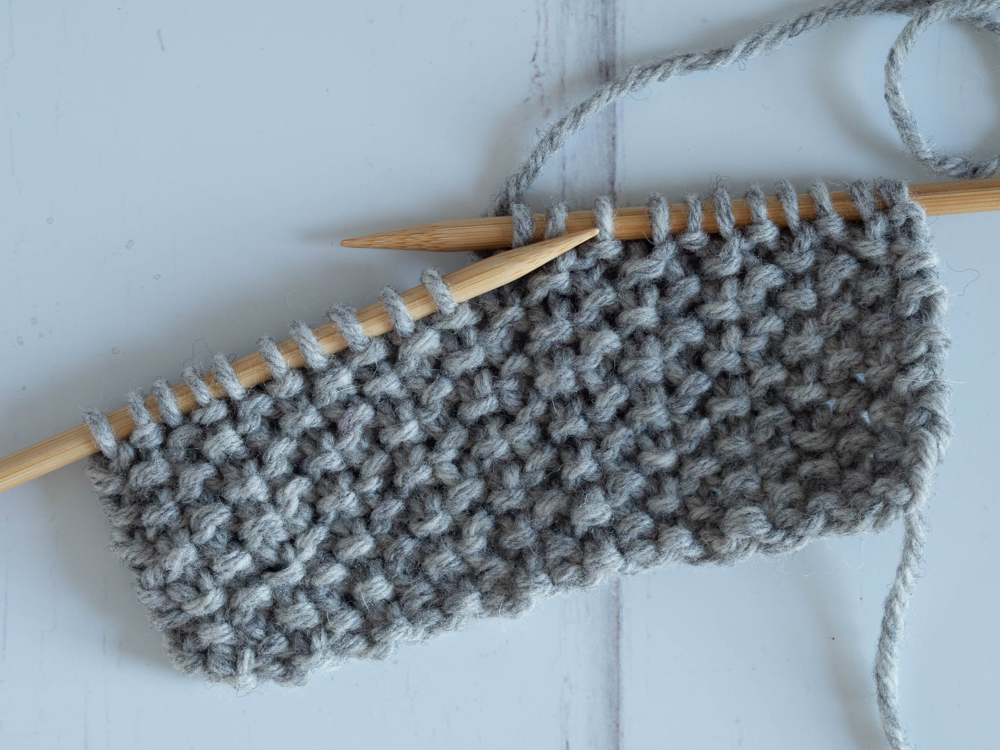 a grey seed stitch swatch on the needles