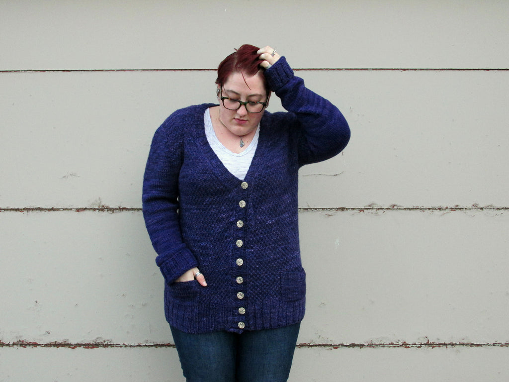 Image of a light skinned woman standing in front of a white wall. She is wearing a dark blue cardigan. Her left hand is in her red brown hair.