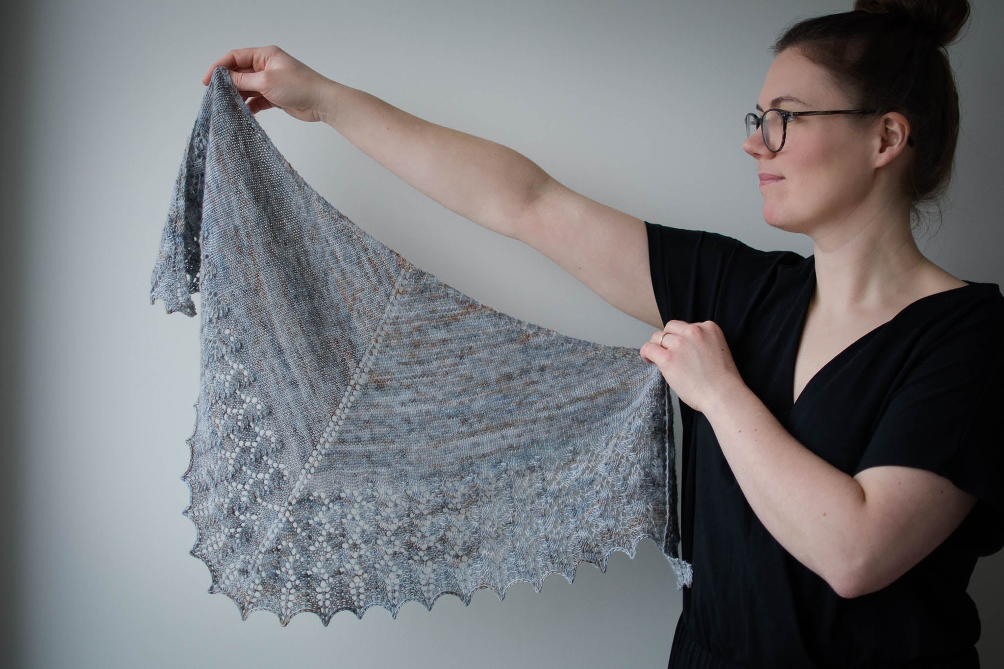 A young white woman wearing a black t-shirt holds up a grey lace shawl, spreading it out to the left side of the image.