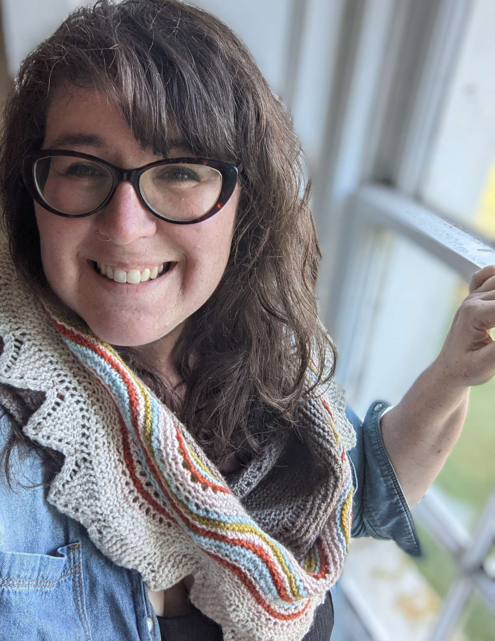 A white woman with long wavy hair and glasses stands indoors in front of a window. She is smiling and wears a neutral shawl with brightly coloured stripes and a blue shirt.