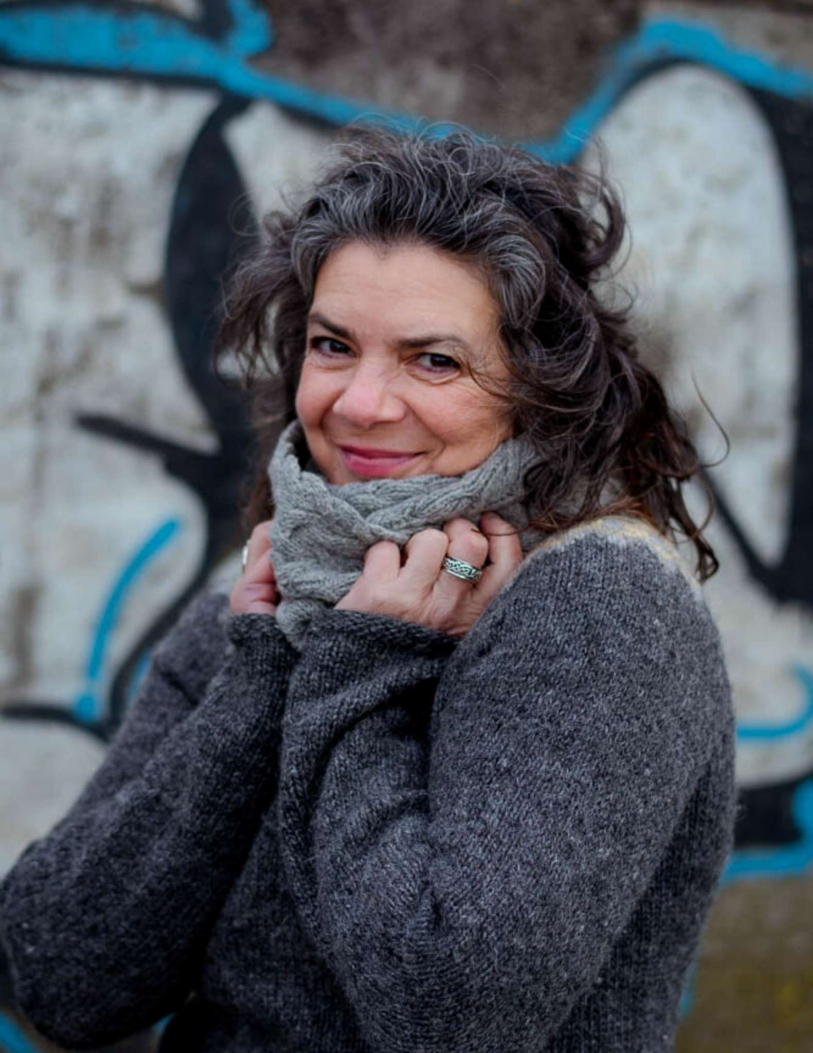 a white woman in her 50s with dark curly hair wears a grey sweater and pale grey cowl. Their hands are held up to the cowl and they are smiling.