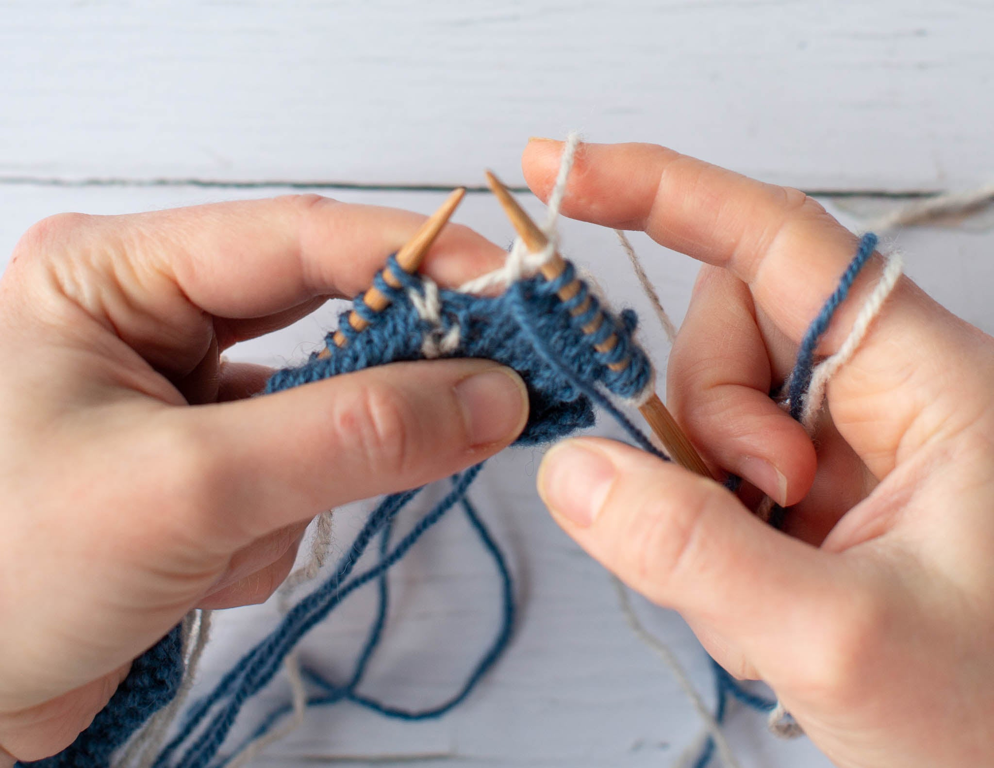 Two white hands holding a blue and white piece of knitting on wooden needles.