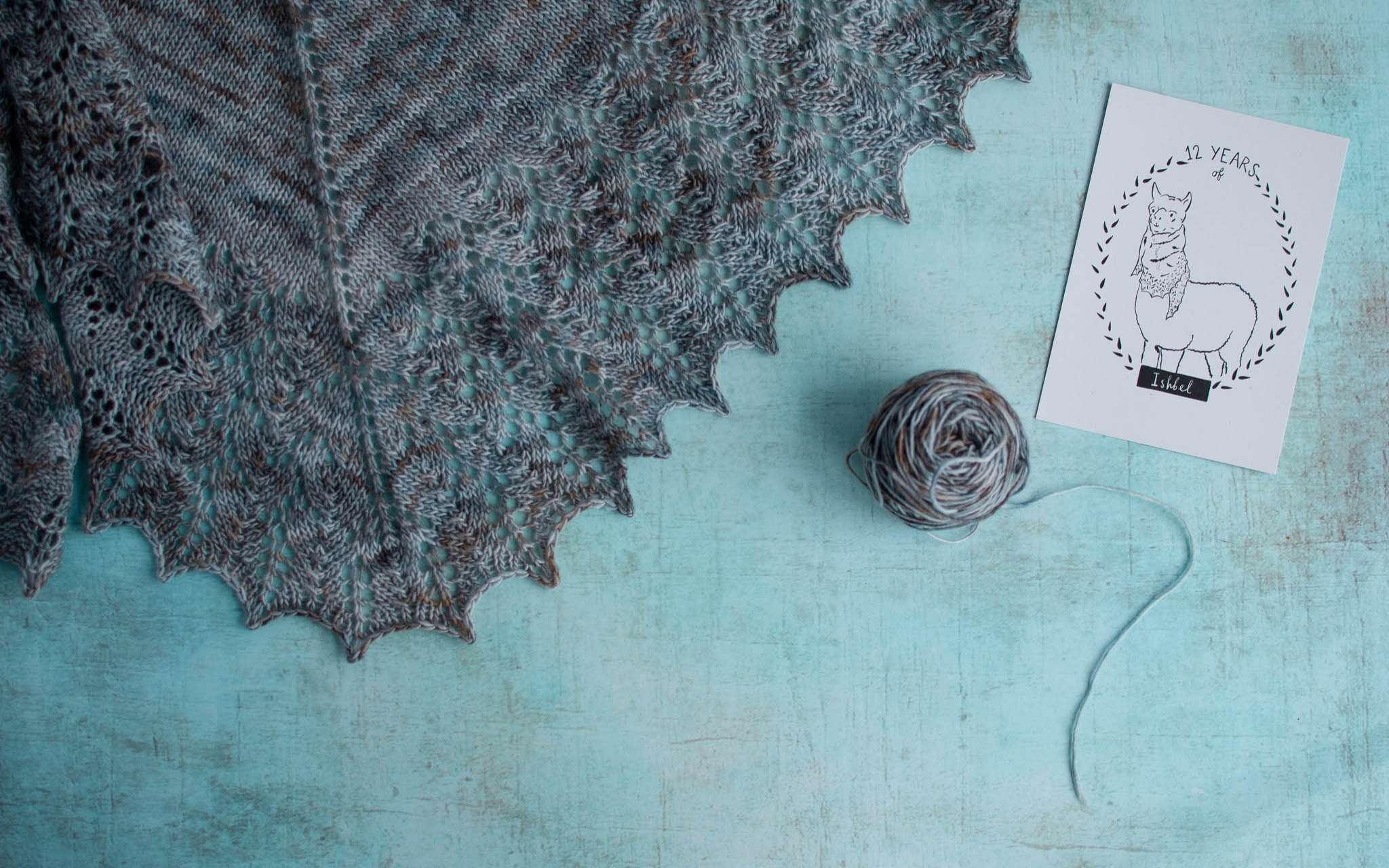A grey lace shawl lies flat on a blue mottled surface, next to a ball of the grey yarn used and a postcard showing an illustration of an alpaca wearing a shawl.