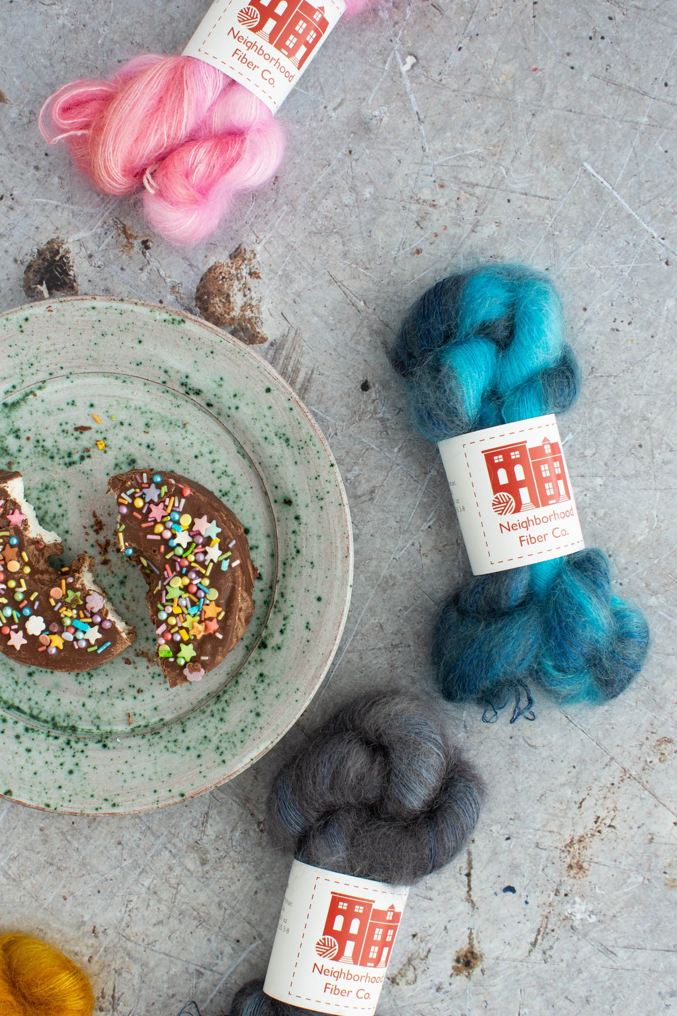 A speckled plate with a chocolate covered donut sits off centre on a scratched grey background. The donut has brightly coloured sprinkles. 4 brightly coloured skeins of hand dyed mohair yarn are scattered around the plate.  Rustic Fingering- 100% Superwash Merino (single ply)