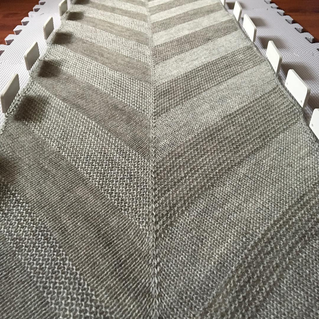 Image of a grey shawl blocking with the garter and stocking stitch sections catching the light differently.