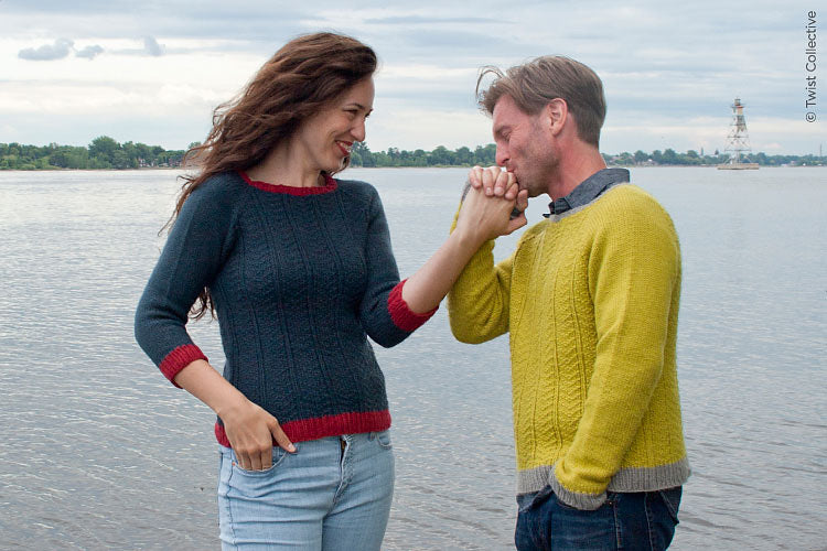 Image of a light skinned man and woman in front of a body of water. The woman is wearing a blue jumper with red edging and the man is wearing a yellow jumper with grey edging. The jumpers have a textured stitch pattern.
