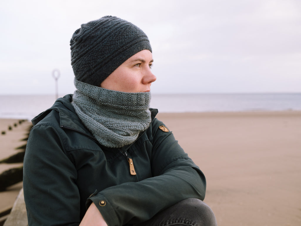 Image of a white skinned woman wearing a dark blue hat and a light blue cowl. She is looking into the distance on a beach while leaning on a breakwater.