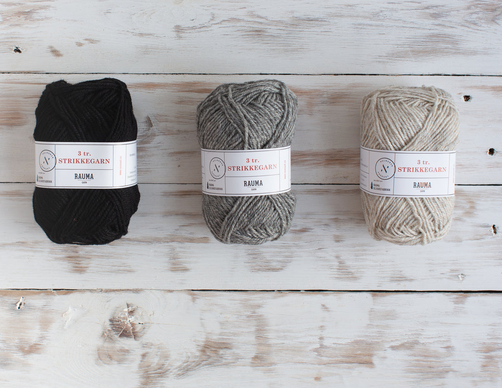 Three balls of Strikke yarn in black, mid grey and light grey. On a white-washed wooden background.