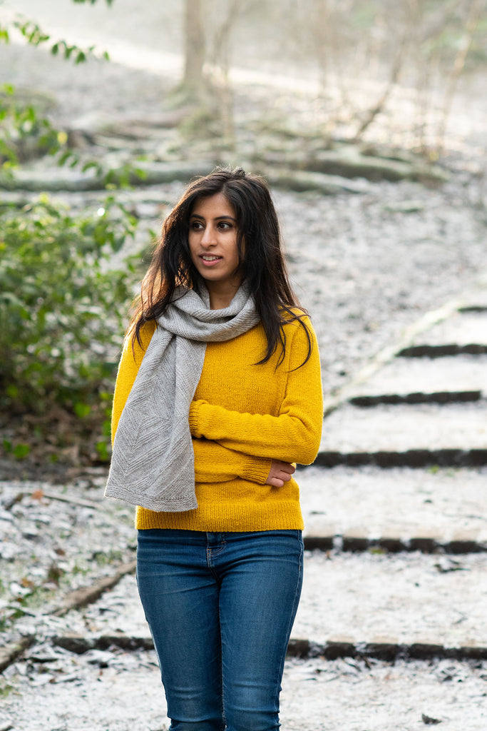 Image of a woman with light brown skin and medium length black hair wearing a yellow sweater and a grey textured scarf