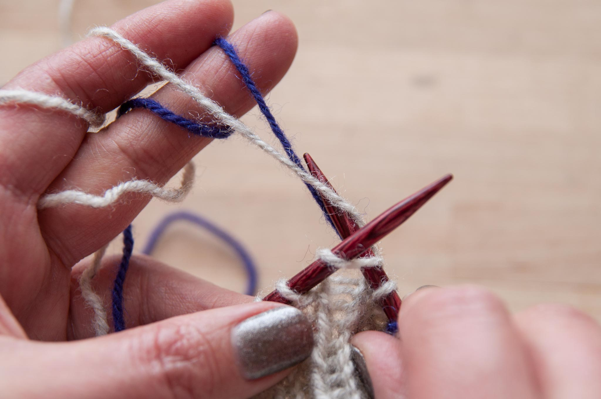 Move the right needle tip below the background colour to pull up a new stitch in the foreground colour.