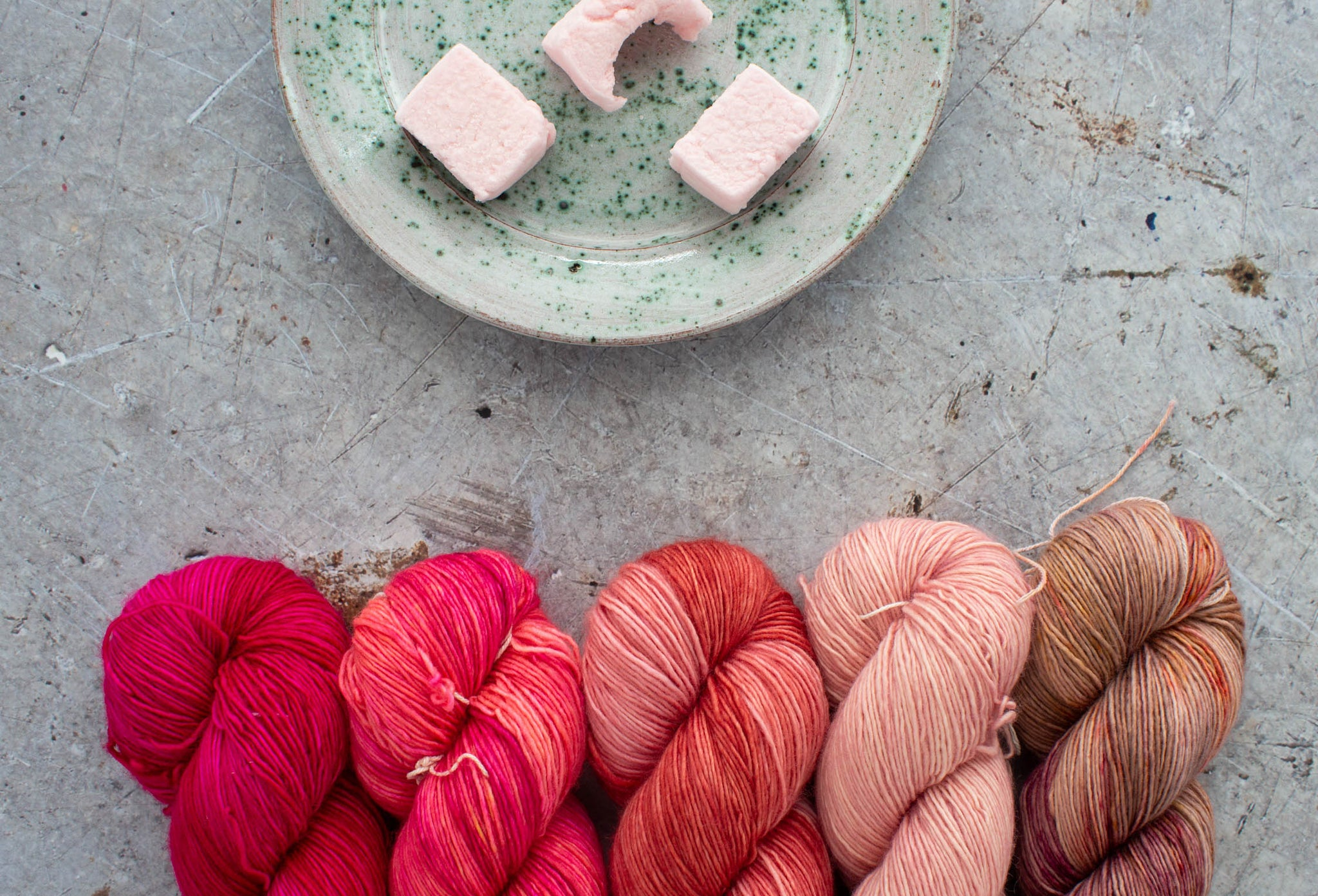 5 skeins of hand dyed yarn in hues of pink line up along the bottom of the image. Above is a speckled plate with pink marshmallows is just above. They are on a scratched metal background.