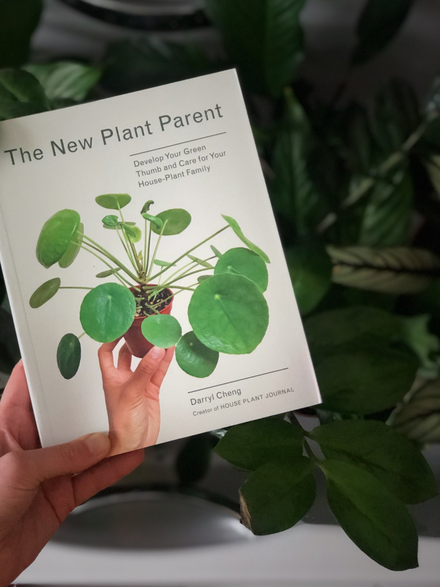 A white skinned hand holding a book called the New Plant Parent over a table covered in greenery.
