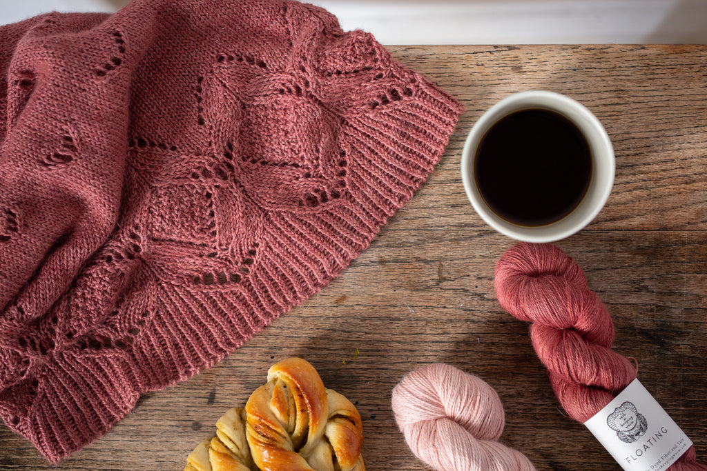 Reddish pink lace cowl draped in the corner of a wooden table next to 2 skeins of Floating yarn in the same colour and a paler version, a cup of coffee and a pastry.