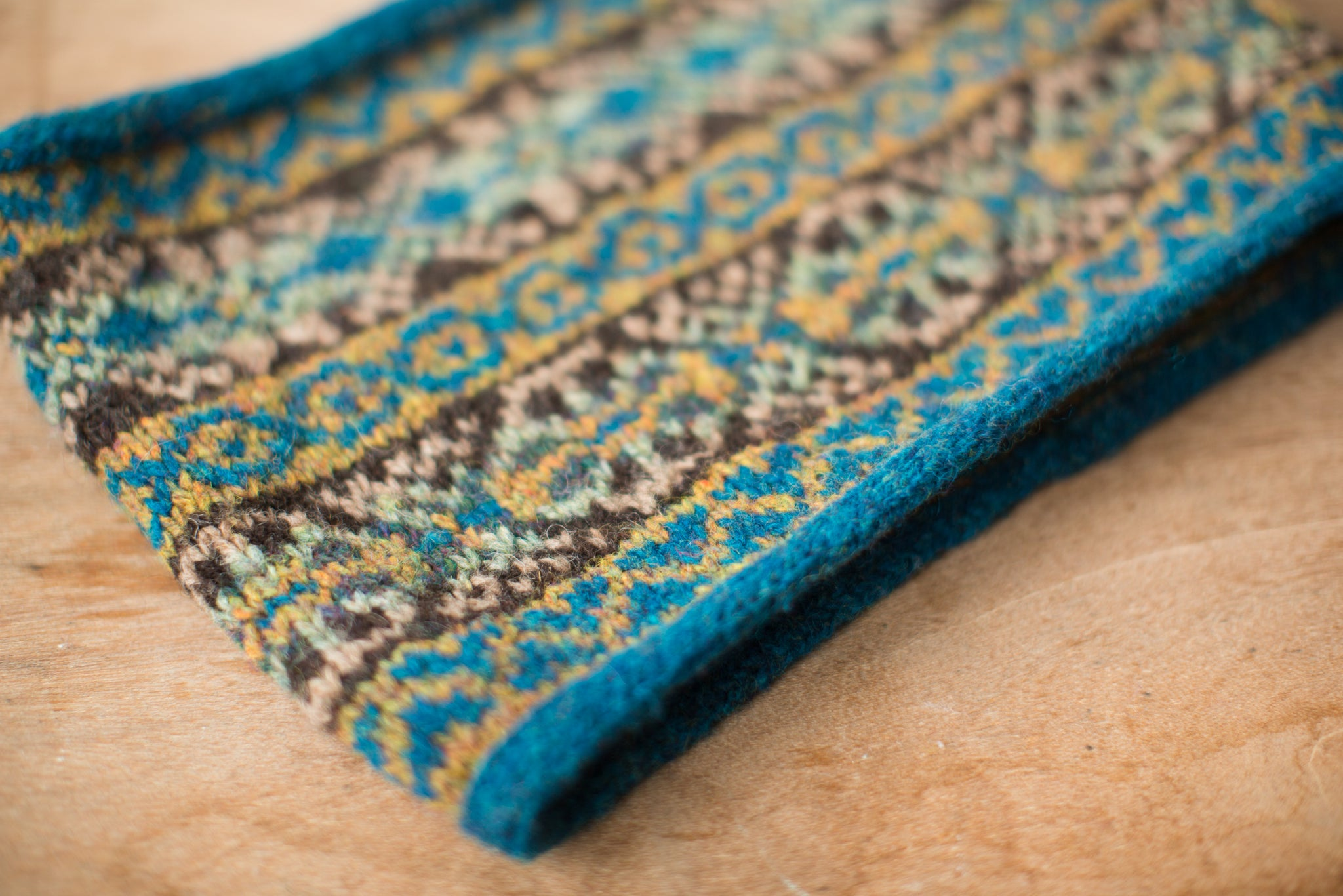 a colourwork cowl in blues, browns and earthy tones lays flat on wooden surface.