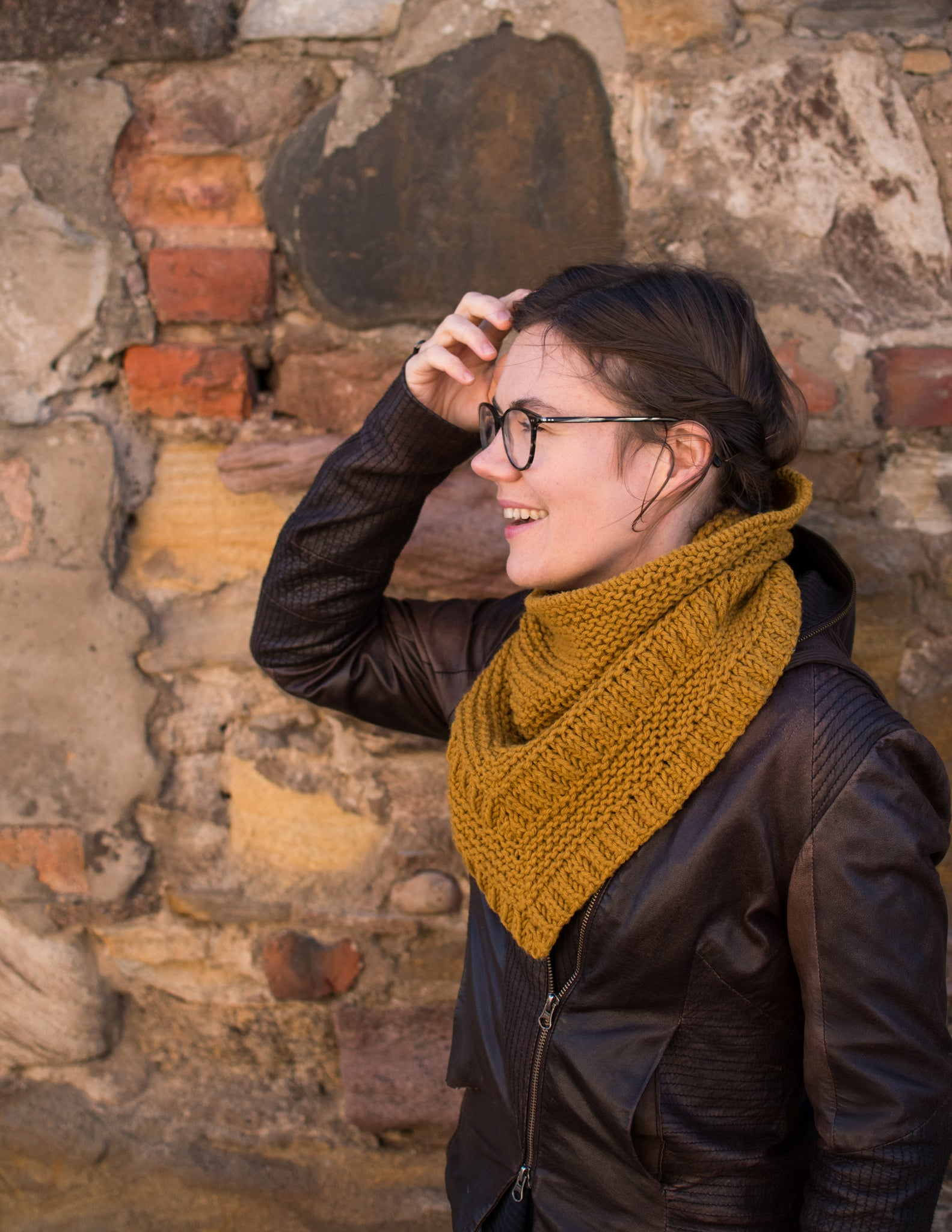 Picture of a white skinned woman wearing a gold bulky cowl. She is facing left against a brick wall.