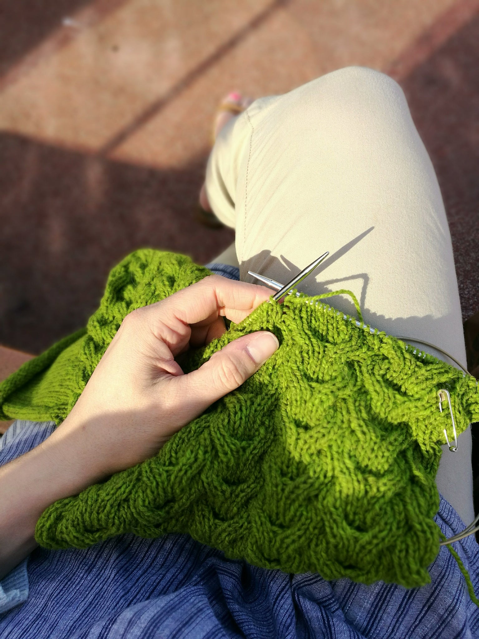 Image of knitting shot from above, in warm sunshine. A white skinned hand holds the needle, the project is a cabled cowl in green yarn.