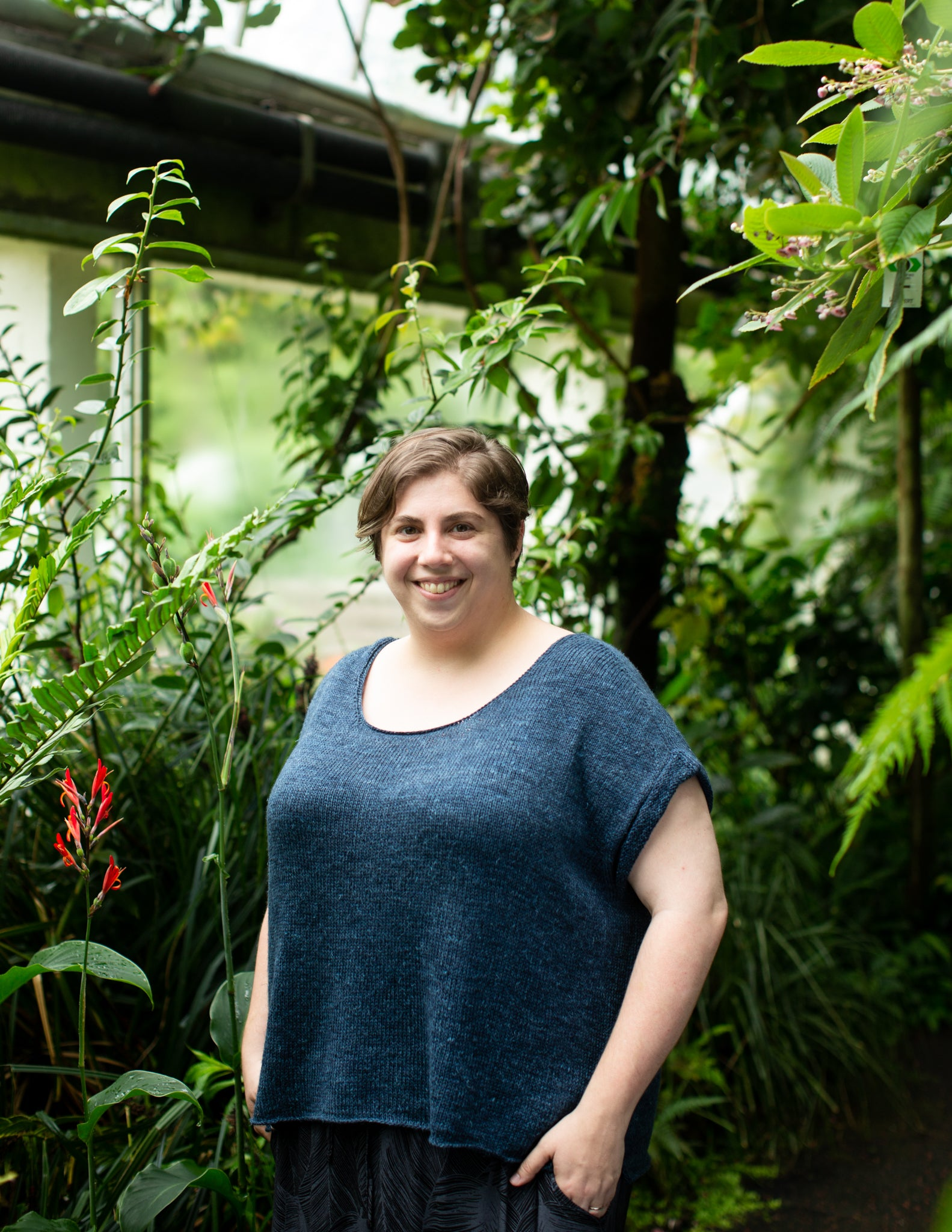 White woman wearing a dark blue inverleith standing in an abundant greenhouse