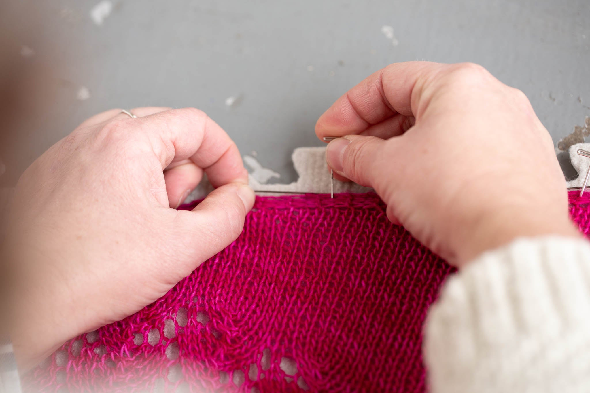The straight edge of shawl is held with blocking wires and being pinned to the blocking mats.