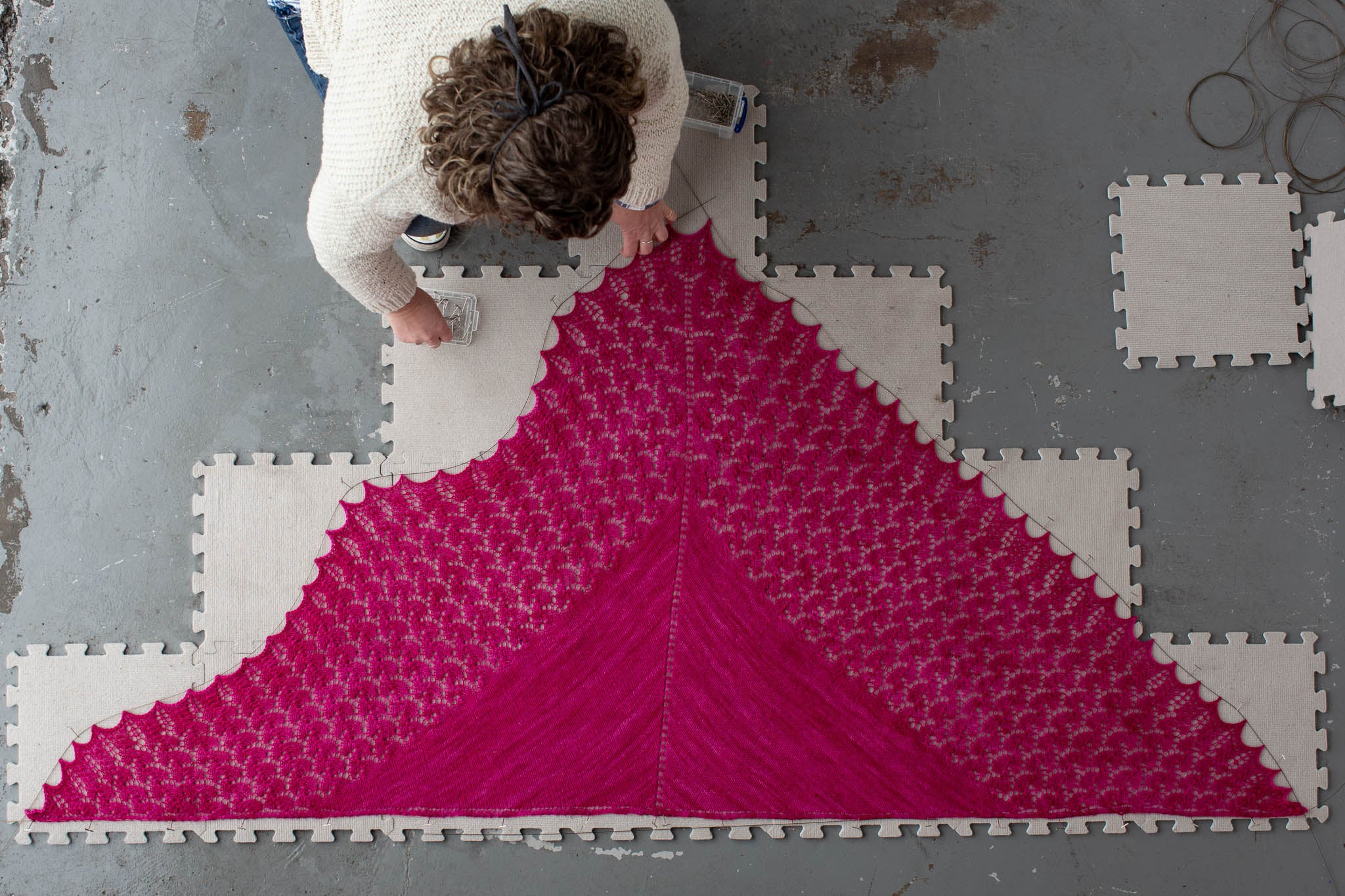 A photo taken from above of an entire triangular pink shawl, partially pinned out on a blocking mat. A white woman with curly brown hair is leaning over the shawl as the remainder is pinned out.