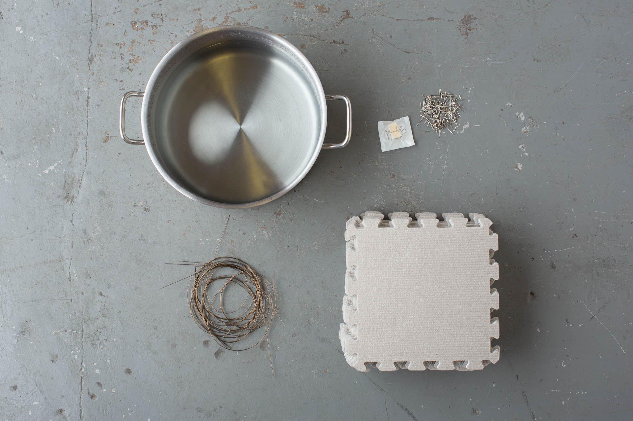 A silver metal pan, a stack of blocking mats and a some blocking wires curled up together are arranged on a flat grey surface.